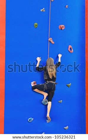 Young girl climbing up secured with rope. Wall is a blue balloon with mounted steps - stock photo