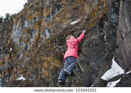 young Girl climbs the rocks - stock photo