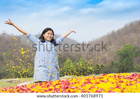 Young girl closed her eyes in happy moment around many flowers petal