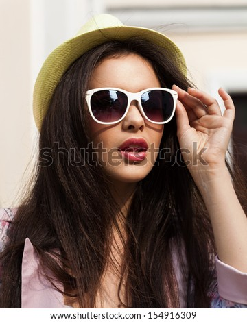 Young girl closeup portrait. Stylish woman posing on the street with interested look and green hat on her head. - stock photo