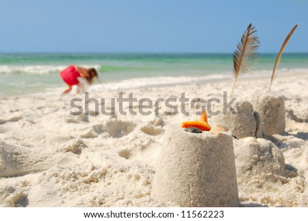 Young girl collecting seashells on beach next to sand castles - stock photo