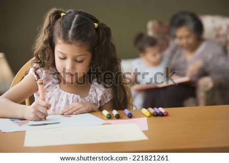 Young girl coloring at table - stock photo