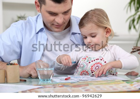 Young girl coloring with dad - stock photo