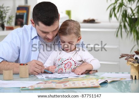 Young girl colouring with her father - stock photo