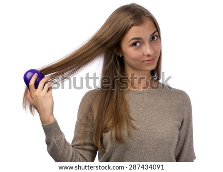 Young girl combing the studio. Isolate on white. - stock photo