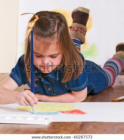 Young girl concentrating on her painting
