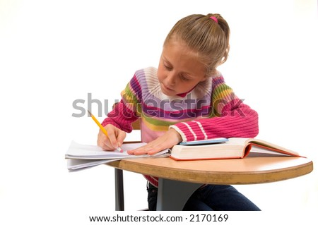 young girl concentrating on work at school desk, correcting a mistake