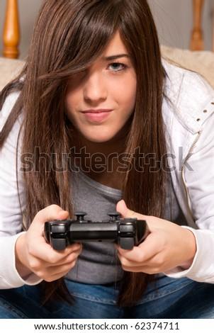 Young girl concentrating playing video-games close-up on sofa at home - stock photo