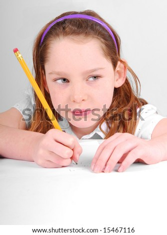 Young girl concentrating while working at desk on schoolwork - stock photo