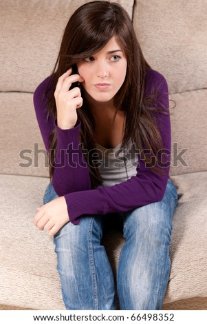 Young girl concerned talking by telephone bad news sitting on sofa - stock photo