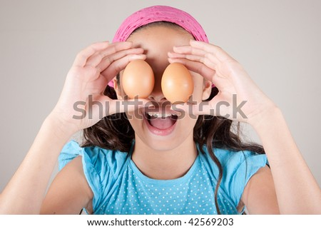 Young girl covering her eyes with eggs - stock photo