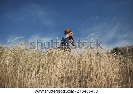 young girl covering her face with a hat outdoors and enjoying the moment. - stock photo