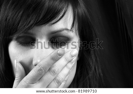 Young girl covering her mouth with her hand in black and white - stock photo
