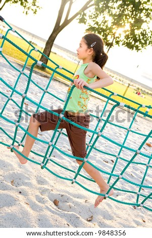 Young girl crossing the rope bridge as part of playground activity. - stock photo