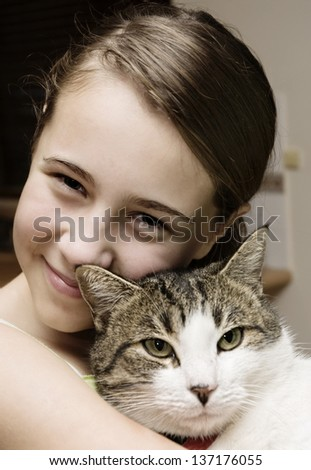 Young girl cuddles her pet cat - stock photo