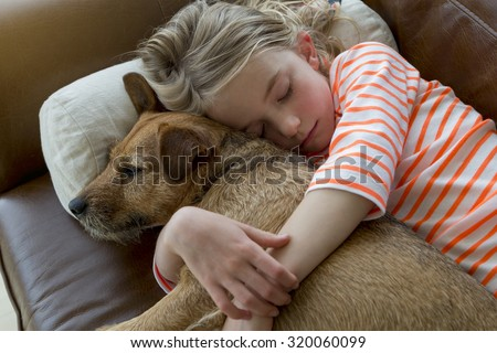 Young girl cuddling her pet dog on a sofa at home. - stock photo