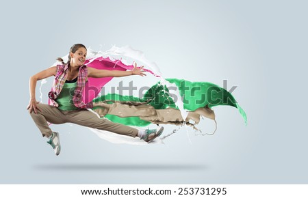 Young girl dancer in jump among color splashes - stock photo