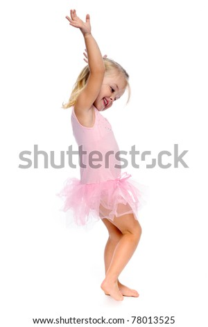 young girl dances ballet in her ballerina tutu, isolated on white in studio