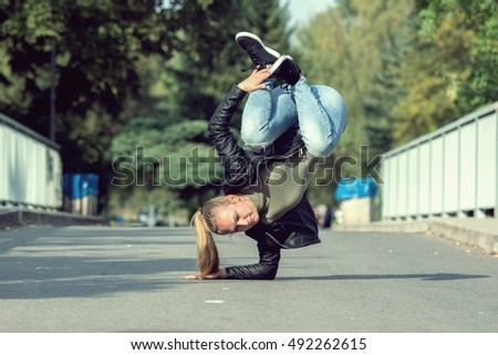 Young girl dancing breakdance on the street