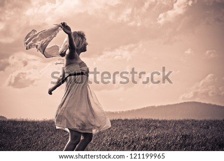 Young girl dancing in the sun with joy and inspiration - stock photo