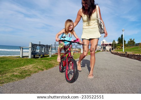 Young girl daughter learning to ride bicycle at the beach with mother having fun and laughing smiling - stock photo
