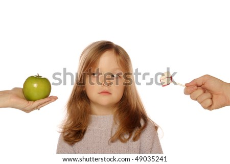 Young girl deciding between apple and sucker (looking at apple)