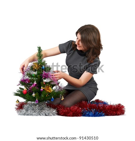 young girl decorates the Christmas tree on a white background - stock photo