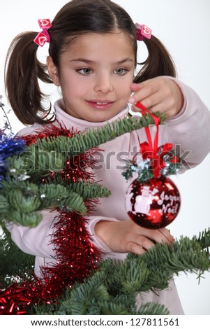 Young girl decorating a Christmas tree - stock photo