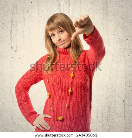 Young girl doing a bad signal over textured background  - stock photo
