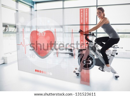 Young girl doing exercise bike with futuristic interface showing electrocardiogram - stock photo