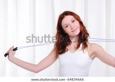 Young girl doing exercises with skipping rope - stock photo