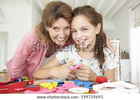 Young girl doing handicrafts with grandmother - stock photo