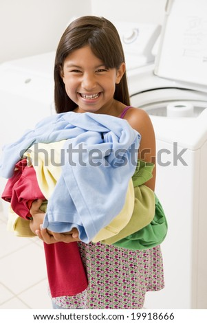 Young Girl Doing Laundry - stock photo