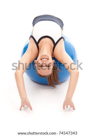Young girl doing pilates exercises on blue fitness ball - stock photo