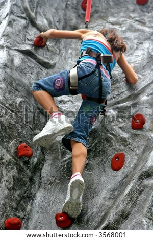 Young girl doing rock climbing in an indoor sports activity hall.