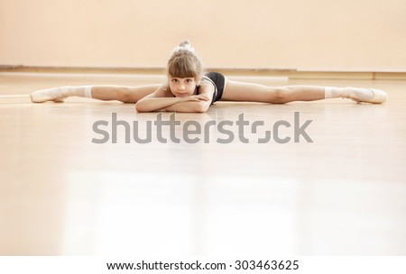 Young girl doing splits while warming up at ballet dance class - stock photo