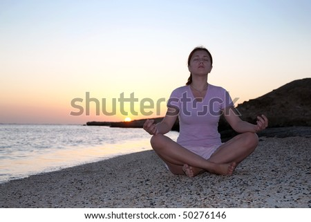 Young girl doing yoga against sunset of a sun