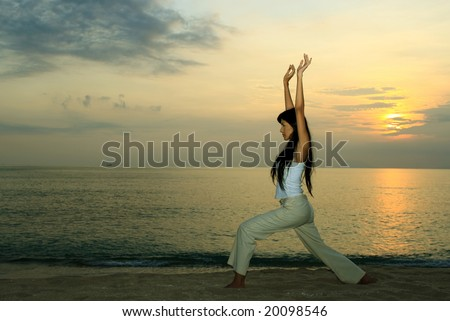 Young girl doing yoga exersice at sunset by the beach - stock photo
