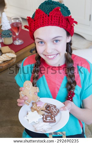 Young girl dressed as an Elf at Christmas Time. She is looking at the camera and smiling and is holding decorated gingerbread men.
