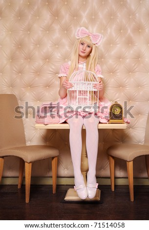 Young girl dressed as doll, sitting on a table with birdcage.