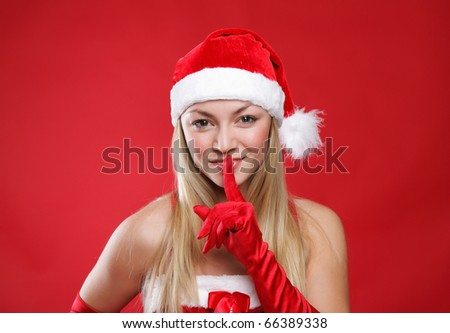 Young girl dressed as Santa Claus on a red background
