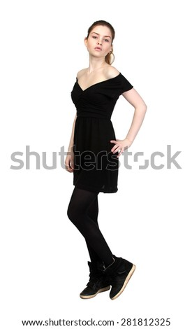 Young girl dressed in casual black dress, black sneakers, isolated on white - stock photo