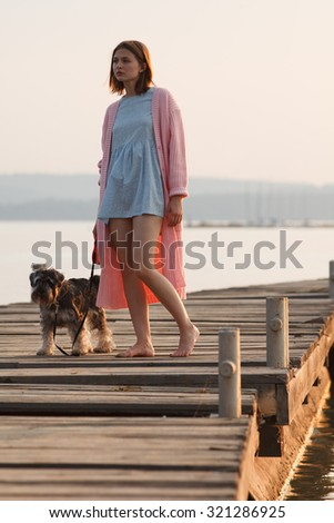 Young girl dressed in romantic style stands  on old wooden pier with a dog on sunset. Professional style and make-up - stock photo