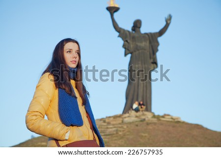 Young girl dressed in Ukrainian national colors standing on the background of monument to liberators and thinks about the fate of the motherland at autumn sunny day