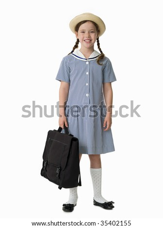 Young girl dressed in uniform holding school bag