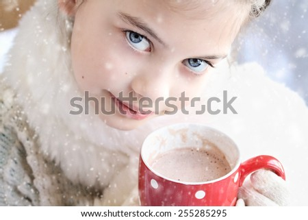 Young girl dressed warmly, drinking hot chocolate outdoor in the winter. Selective focus on child's eyes with extreme shallow depth of field. - stock photo