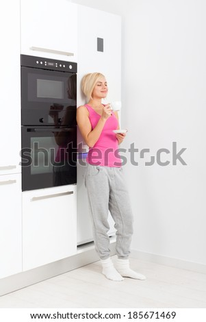 young girl drink coffee standing at modern bright white kitchen appliance, woman closed eyes dream - stock photo