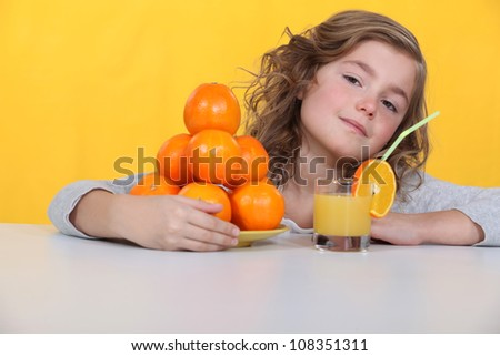 Young girl drinking a glass of orange juice - stock photo
