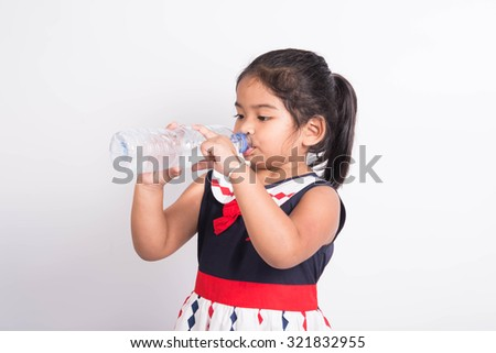 Young girl drinking fresh water from a bottle on white background