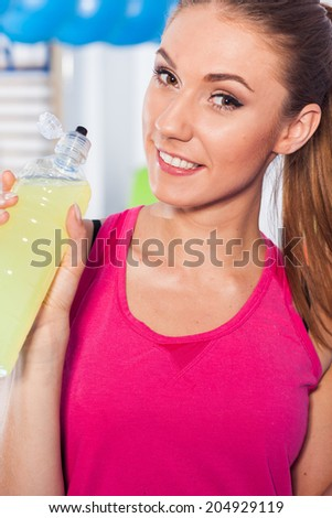 Young girl drinking isotonic drink, gym. She is happy and full of positive emotion